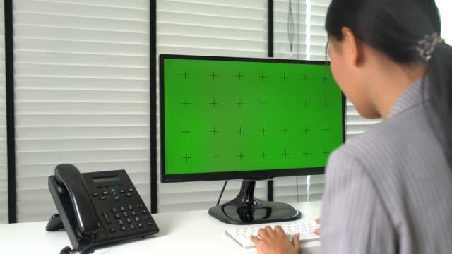 事務所に緑色の画面のコンピューターを使用してアジアの実業家 - デスクトップ型パソコン点の映像素材/bロール
