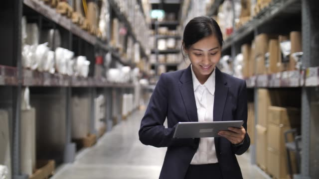 asian businesswoman using digital tablet checking the packages on shelves in warehouse - retail manager stock videos & royalty-free footage