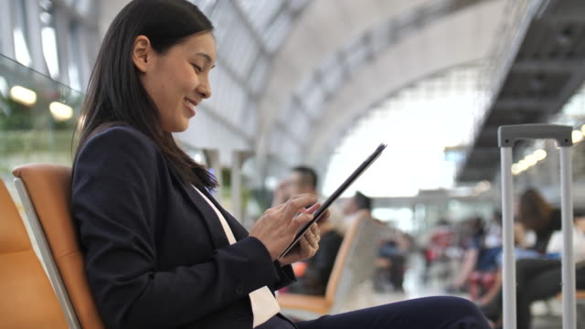 asian businesswoman using digital tablet in airport - usare un tablet video stock e b–roll