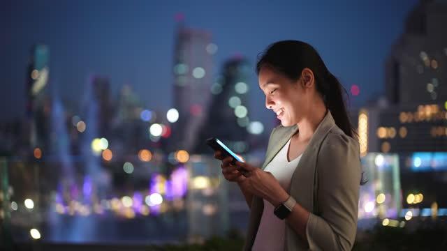 vídeos de stock, filmes e b-roll de mulher de negócios asiática usando telefone na noite da cidade, mídias sociais, celular, mensagens de texto - esperar