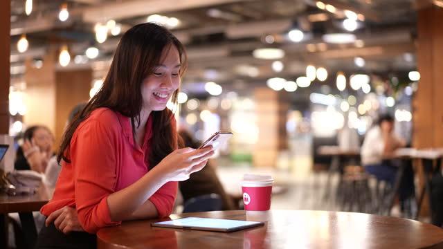 vídeos de stock, filmes e b-roll de mulher de negócios asiática usando dispositivo inteligente no café - portable information device