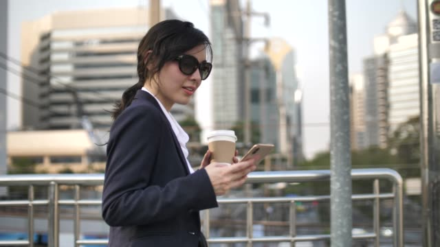 asian businesswoman using smart phone and talking in city - soft focus stock videos & royalty-free footage