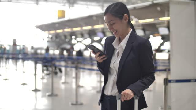 空港でスマートフォンを使うアジアのビジネスウーマン - 出張点の映像素材/bロール