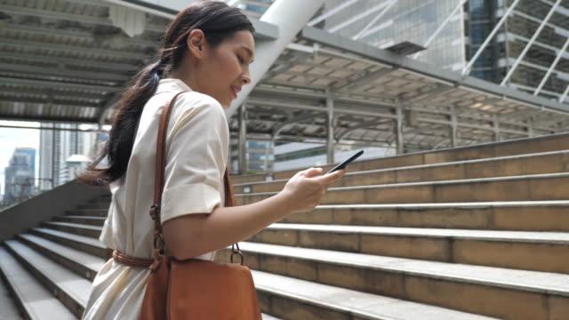 都市でスマートフォンを使用してアジアのビジネスウーマン - 階段点の映像素材/bロール