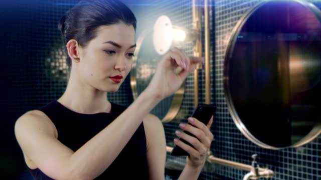 vídeos de stock e filmes b-roll de asian businesswoman using smart phone in elegant bathroom - ecrã tátil