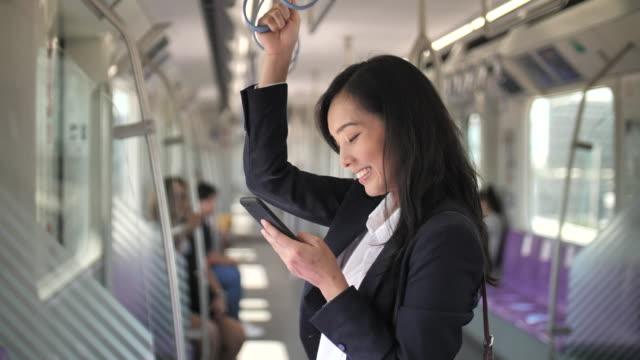 電車の中でスマートフォンを使うアジアのビジネスウーマン - 公共交通機関点の映像素材/bロール