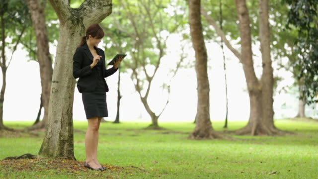 WS Asian businesswoman using tablet device outdoors in park