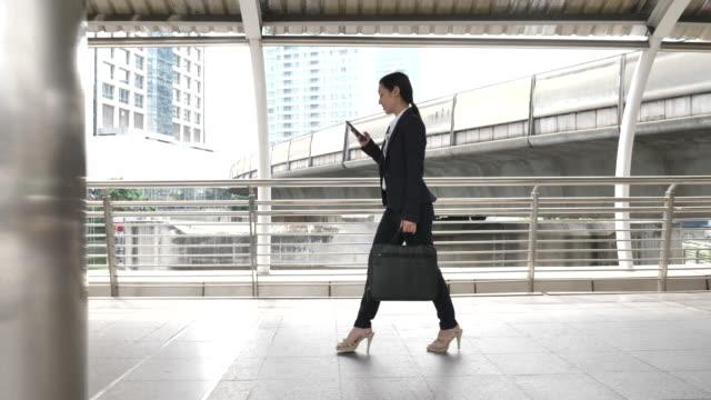 slow motion asiatische geschäftsfrau zu fuß zur arbeit und mit smartphone - elegante kleidung stock-videos und b-roll-filmmaterial