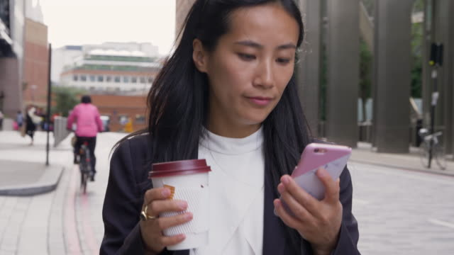 asian businesswoman walks, while looking at smart phone, in city. - take away food stock videos and b-roll footage