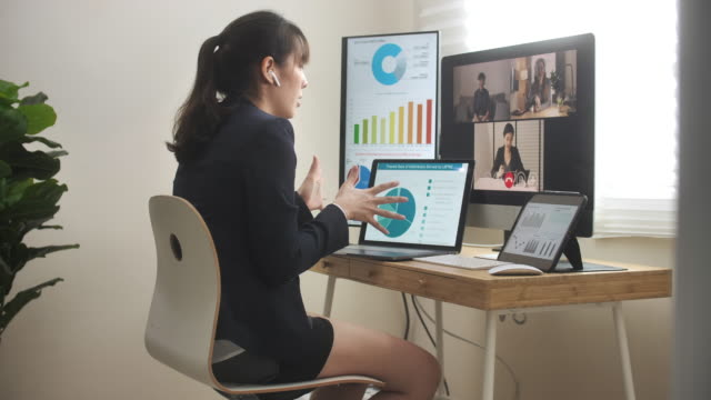 vídeos de stock e filmes b-roll de asian businesswoman wearing a half suit and business clothing on top and having video conference meeting with her colleague - vestuário de trabalho formal