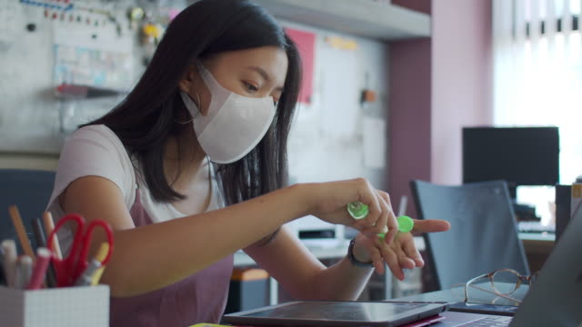 asian businesswoman wearing mask use alcohol-based hand wash gel to clean the hands before starting work in home office background.wash hands clean and wear a mask to prevent the spread of the virus connect with others.4k uhd. - place of work stock videos & royalty-free footage