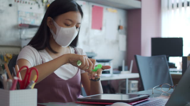 asian businesswoman wearing mask use alcohol-based hand wash gel to clean the hands before starting work in home office background.wash hands clean and wear a mask to prevent the spread of the virus connect with others.4k uhd. - micro organism stock videos & royalty-free footage