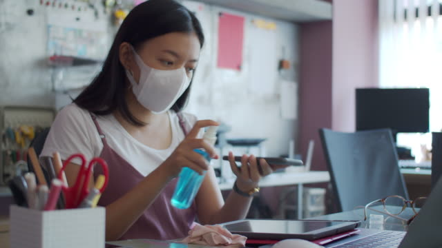asian businesswoman wearing mask use alcohol-based hand wash spray to clean the tablet and smartphone before starting work in home office background.wash hands clean and wear a mask to prevent the spread of the virus connect with others.4k uhd. - spraying stock videos & royalty-free footage