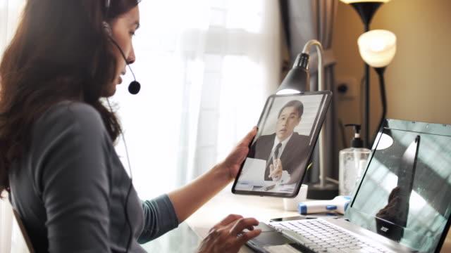stockvideo's en b-roll-footage met aziatische onderneemster die videovraag met haar werkgever op digitale tablet thuis werkt - kantoorkamer