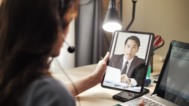 asian businesswoman working video call with her boss on digital tablet at home - speech stock videos & royalty-free footage