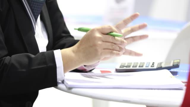stockvideo's en b-roll-footage met aziatische zakenvrouwen houdt een pen en analyse documenten op kantoor tafel met laptop computer en grafiek financiële diagram werken op de achtergrond - graph