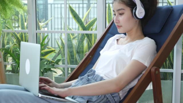 asiatische geschäftsfrauen verwenden notebooks und tragen kopfhörer für online-meetings und arbeiten von zu hause aus im garten. - weibliche angestellte stock-videos und b-roll-filmmaterial