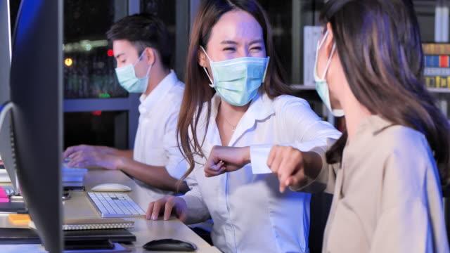"""asiatische geschäftsfrauen tragen gesichtsmaske beim gruß mit ellbogenstoß im büro zu arbeiten in der nacht der arbeit spät,nach covid-19 pandemie. ein arbeitstag im """"neuen"""" büro - weibliche angestellte stock-videos und b-roll-filmmaterial"""