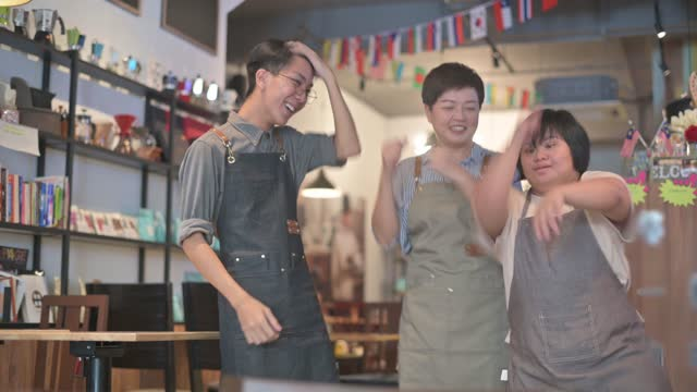 vidéos et rushes de café asiatique vers le bas syndrome handicap employé et propriétaire danse temps de liaison dans le café heureusement - satisfaction