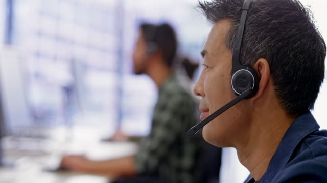 asian call center agent talking with a customer - supporto tecnico video stock e b–roll