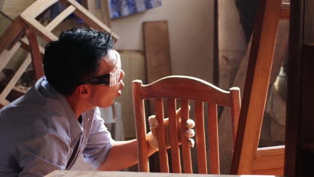 vídeos de stock, filmes e b-roll de carpinteiro asiático lixando cadeiras de madeira com lixa e soprando poeira. - lixadeira