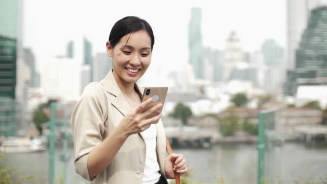 vídeos de stock, filmes e b-roll de mulher casual asiática usando telefone inteligente - câmera seguindo movimento