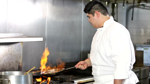 Asian chef with hot flaming pan in commercial kitchen