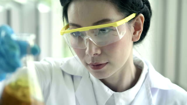 Asian Chemist pouring cosmetic oil : Body care production