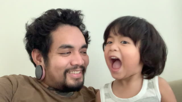 pov:笑うスマートフォンのカメラで自分撮りを取るアジアの子供とヒップスターの男 - photo messaging点の映像素材/bロール