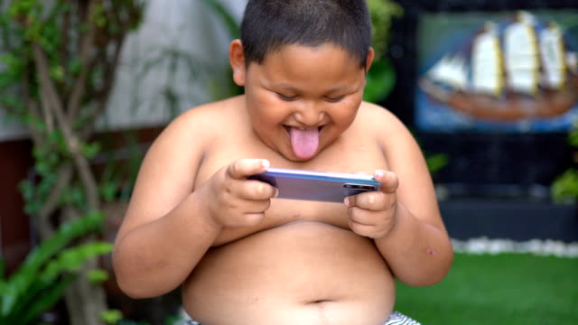 asian child boy are addictive playing mobile phones - overweight stock videos & royalty-free footage