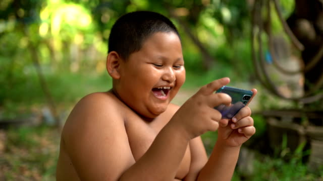 asian child boy are addictive playing mobile phones - geographical locations stock videos & royalty-free footage