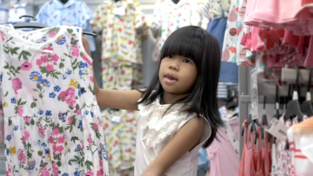 Asian child choosing clothes