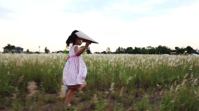 asian child girl and father with a kite running and happy on meadow in summer in nature,slow motion - kid with kite stock videos & royalty-free footage