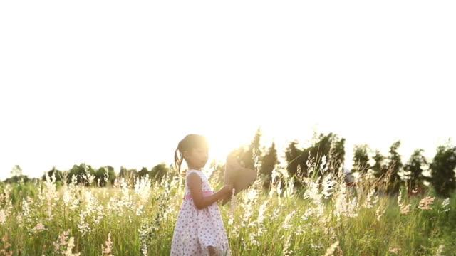 自然の中で夏の草原でカイトランニングと幸せなカイトを持つアジアの子供の女の子と父親、スローモーション - 小さい点の映像素材/bロール