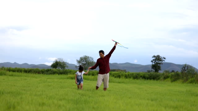 asian child girl and father with a kite running and happy on meadow in summer in nature - kite toy stock videos and b-roll footage