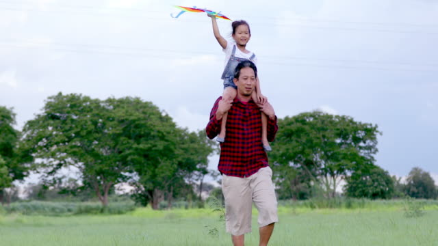 Asian child girl and father with a kite running and happy on meadow in summer in nature
