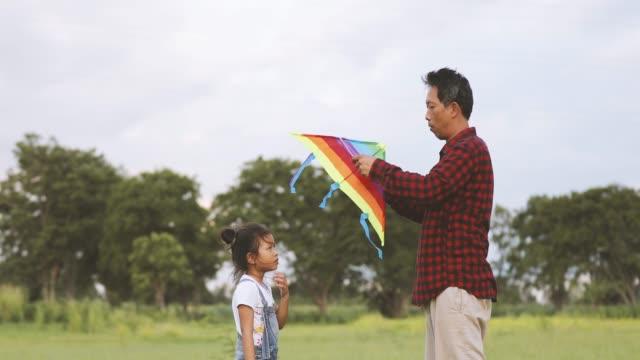 vídeos de stock, filmes e b-roll de menina criança asiática e o pai com uma pipa de execução e feliz no prado no verão na natureza - pipa brinquedo