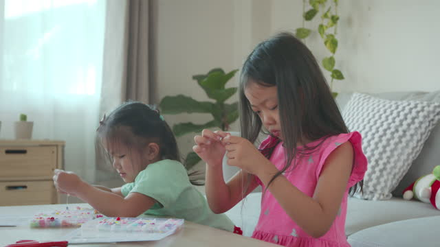asian child girl and friend threading beads onto a string together with intention and fun in home. kid creating handmade bracelets to develop hand motility - string stock videos & royalty-free footage