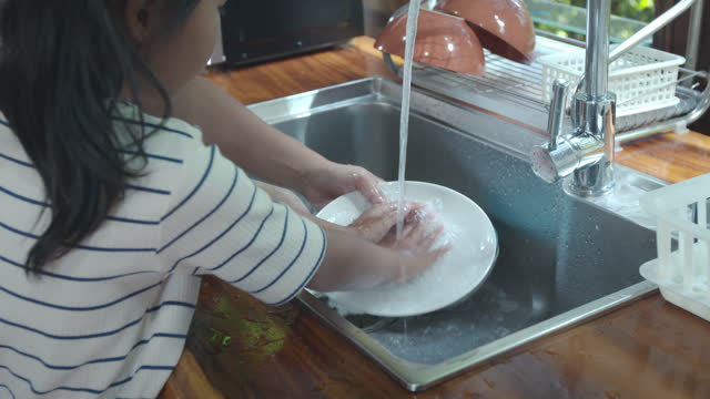 asian child girl and her mother helping clean up and washing dishware after finished eating together in the kitchen at home. - utensil stock videos & royalty-free footage