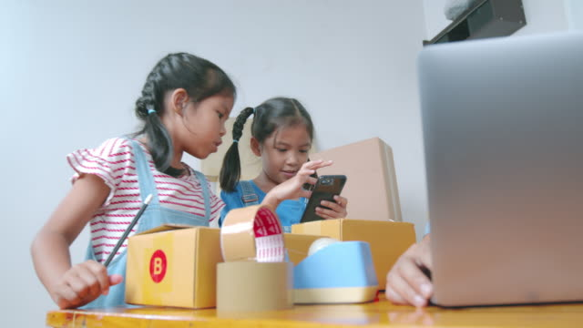 asian child girl is writing address into the box to help parent prepares delivery box for the online customer while mother using laptop computer taking receive and checking online purchase shopping order. - selling stock videos & royalty-free footage