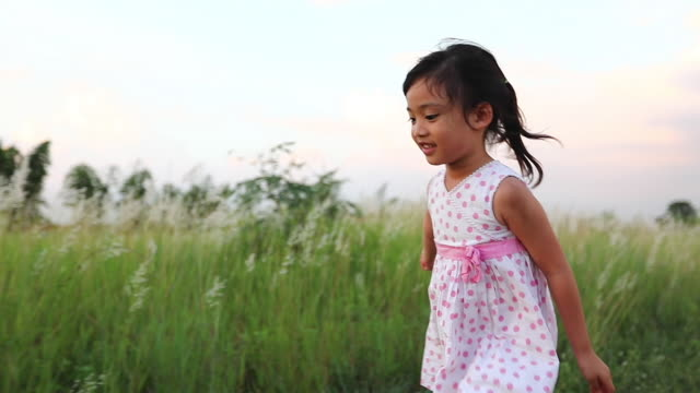 asian child girl running and happy on meadow in summer in nature,slow motion - ethnicity stock videos & royalty-free footage