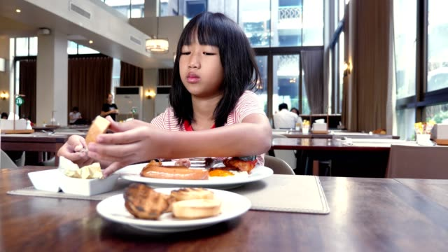 asian child girls eating breakfast in cafeteria. - breakfast stock videos & royalty-free footage