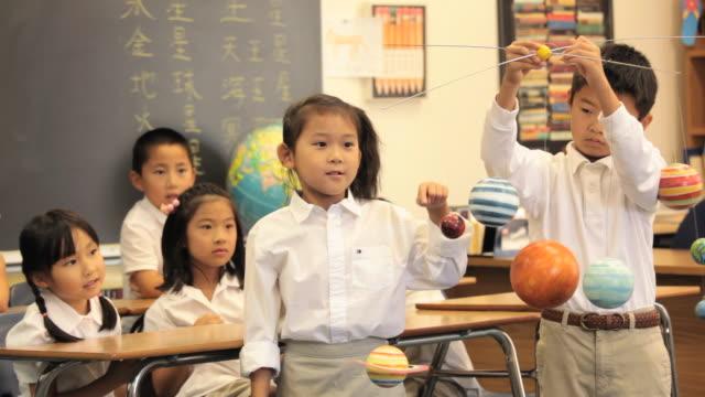 vídeos y material grabado en eventos de stock de asian child in classroom presenting globe to camera / richmond, virginia, usa - globo terráqueo para escritorio