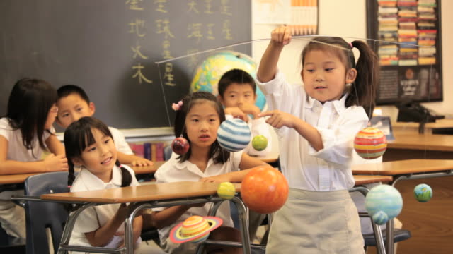 Asian Child in Classroom Presenting Model Solar System to Camera / Richmond, Virginia, USA