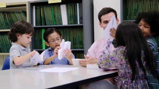 vidéos et rushes de asiatique enfant apprendre à plier du papier avec l'enseignant, art du pliage de papier. - origami