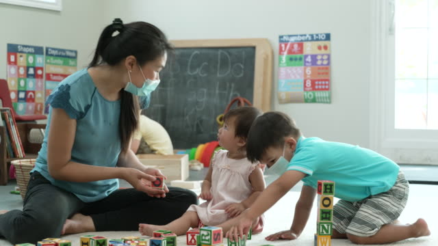 asian child playing with blocks at daycare while wearing masks - child care stock videos & royalty-free footage