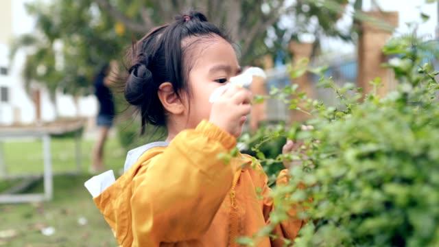 asian child standing in nature scene picking flower