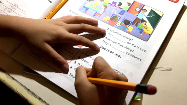 asian child writing  the english homework at home - üben stock-videos und b-roll-filmmaterial