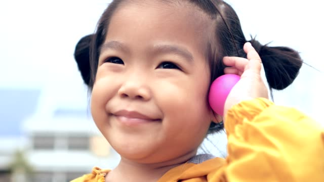 Asian child/girl close up face smiling holding pink ball/toy