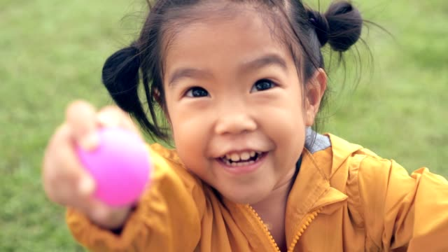 Asian child/girl close up face smiling holding show pink ball/toy